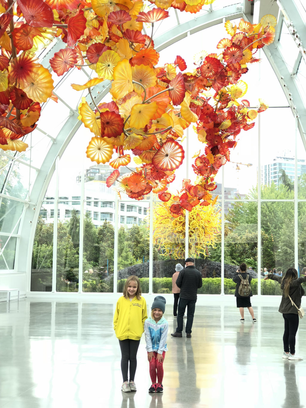 Girls standing under blown glass flowers at the Chihuly Garden and Glass Museum