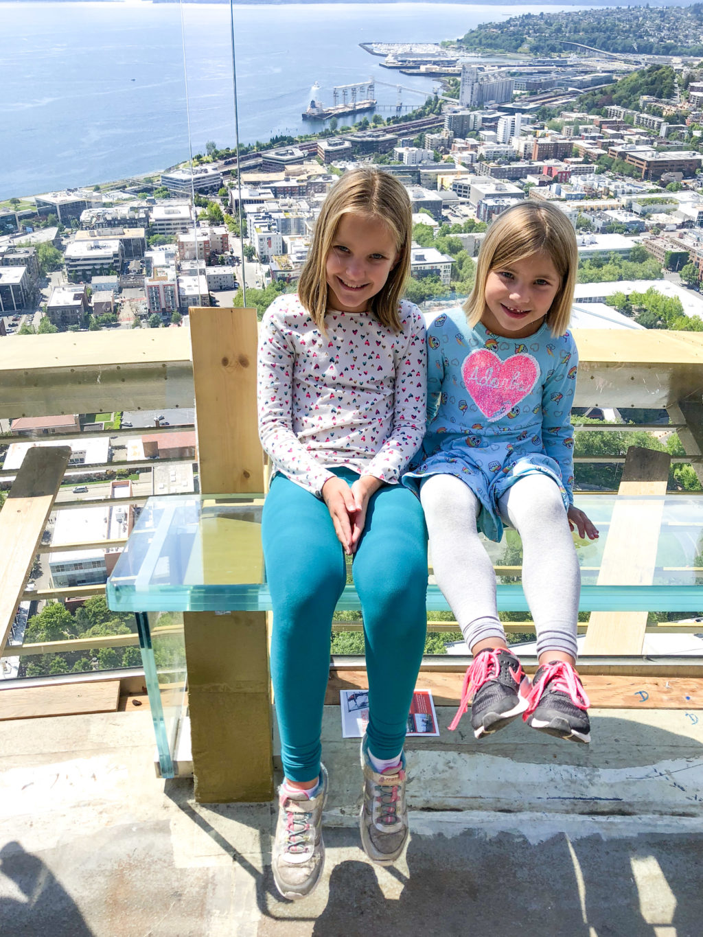 Girls sitting on glass benches at the top of the Space Needle