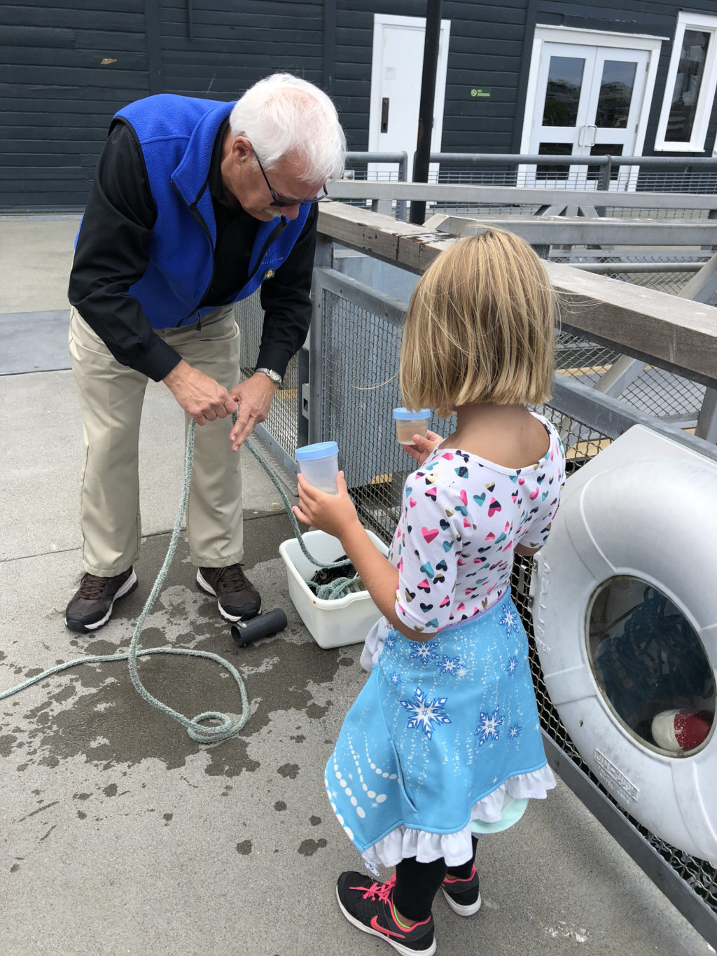 Young girl helping marine biologist from the Seattle Aquarium