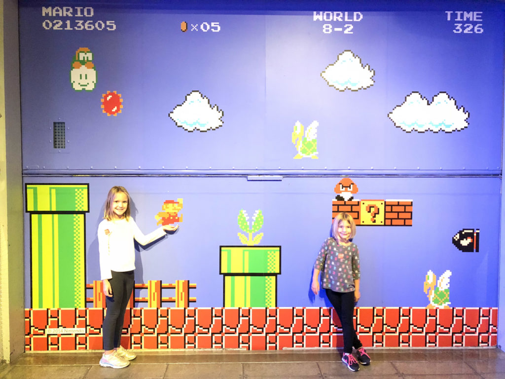 Girls standing in front of Museum of Pop Culture Nintendo wall