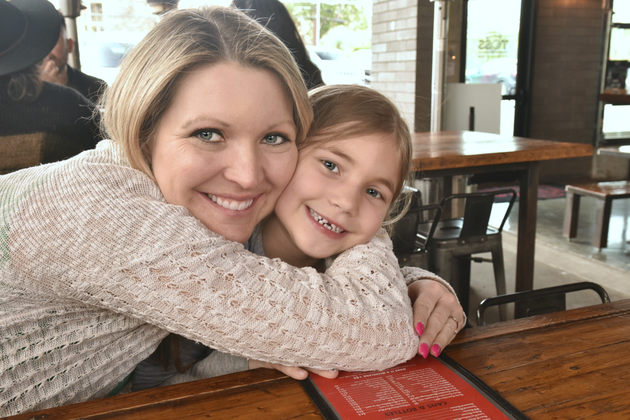 Mom squeezing daughter's neck at restaurant.