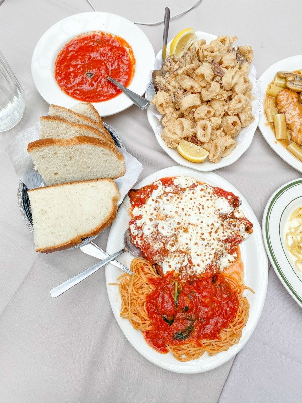 Italian appetizers on table - bread, calamari, chicken parmigiana, marinara