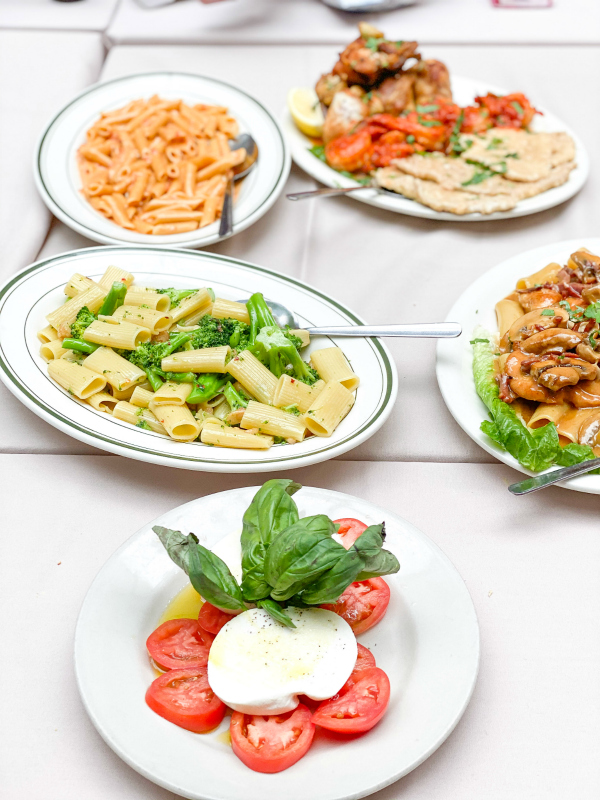 Caprese salad, penne vodka, and other plated Italian dishes