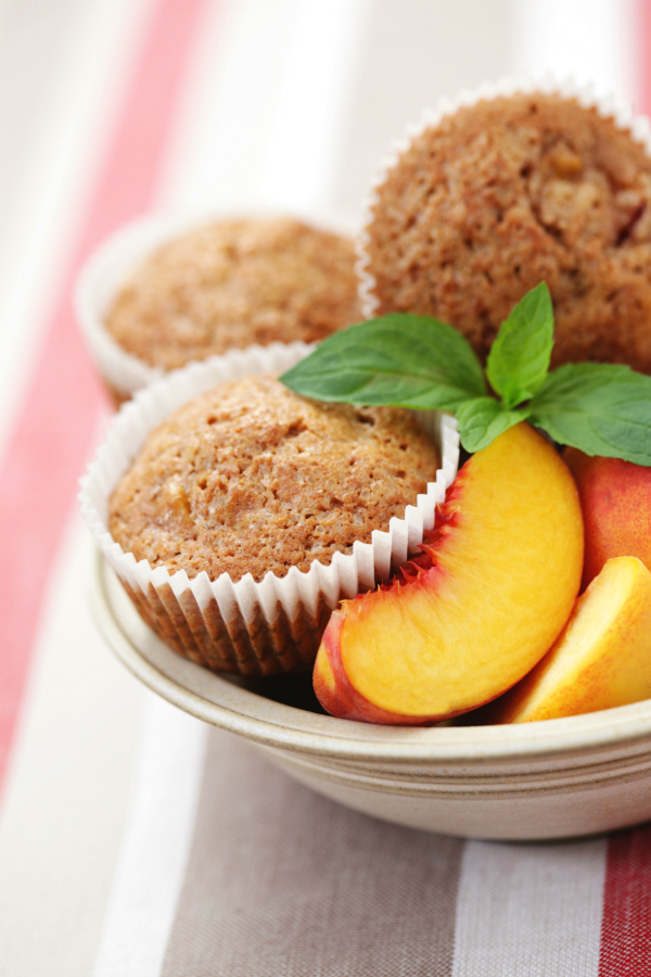 Spiced peach muffin cups on plate with striped tablecloth