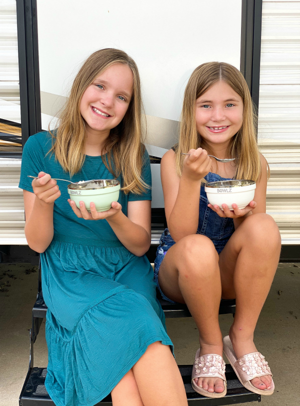 girls eating ice cream outside of travel trailer while camping