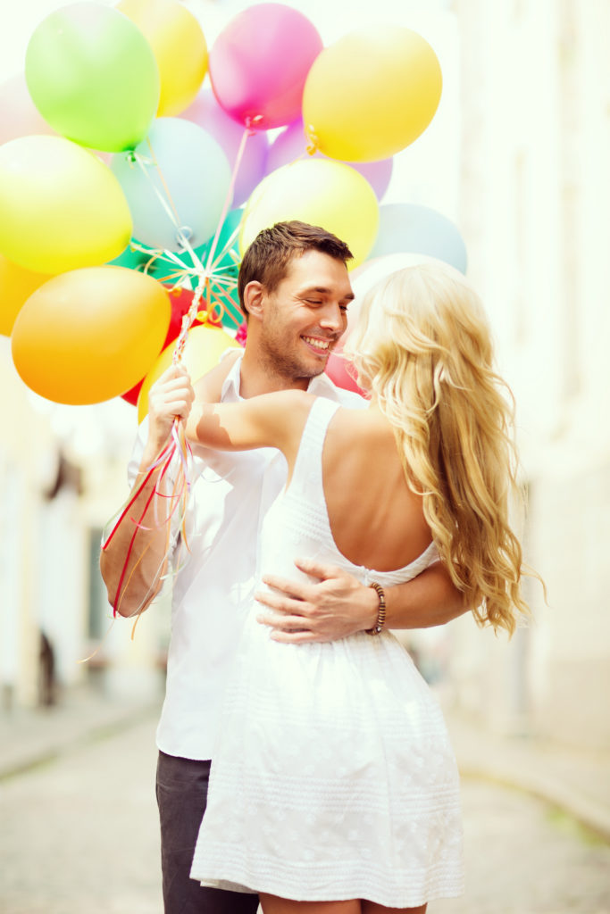 couple before marriage with colorful balloons in the city