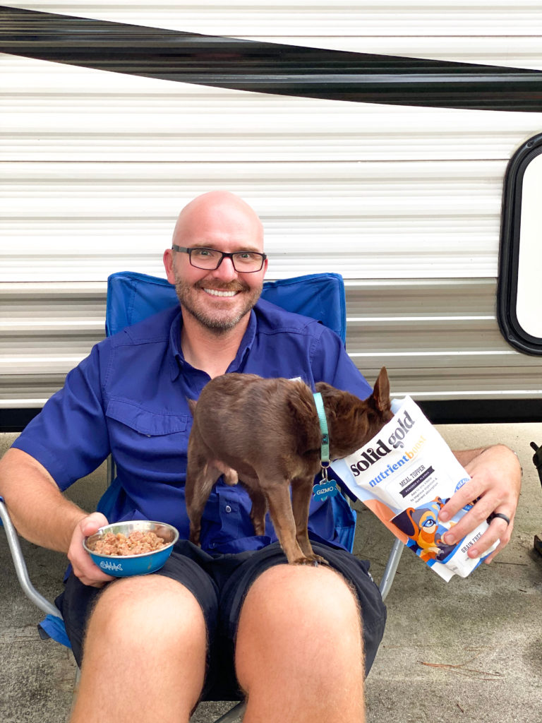 man holding dog eating with food in dog food bag