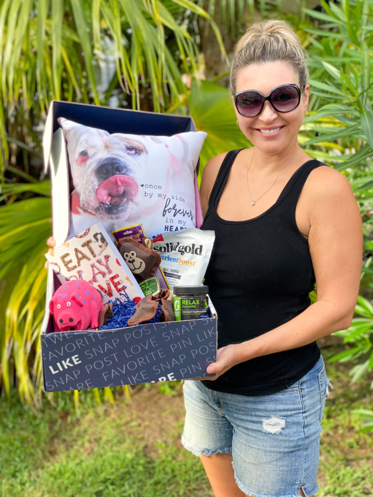 woman holding box with gift ideas for dogs and dog moms