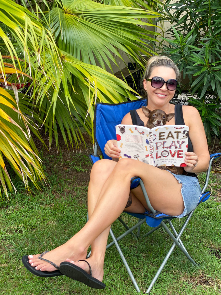 woman outside in camping chair holding dog and reading book - gift ideas for dogs and dog moms